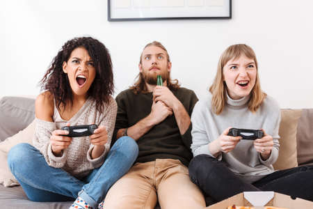 Excited girls playing video games on sofa while boy near amazedly looking on it drinking beer