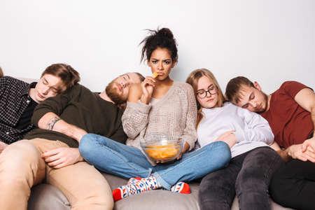 Joven dama enojada mirando tristemente a puerta cerrada y comiendo patatas fritas mientras sus amigos duermen cerca de casa