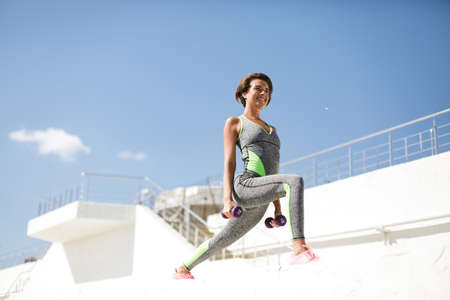 Beautiful smiling woman in modern gray sport suit doing exercise with dumbbells