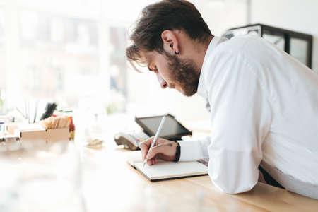 Barista cuidadosamente tomando notas en el trabajo en la cafetería. Foto de archivo