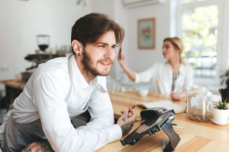 Barista thoughtfully looking aside at the counter while girl using her mobile phone in coffee shop