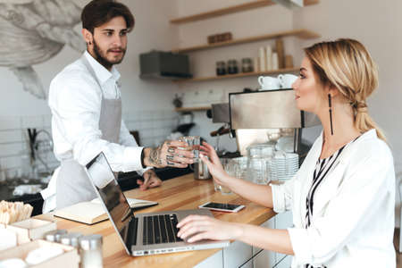 Young barista in apron and white shirt giving glass of water to pretty girl