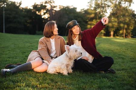 Hermosas chicas tomando selfie en celular mientras pasa tiempo con lindo perro en el parque Foto de archivo