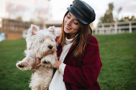 Belle dame en bonnet noir et manteau tenant dans les mains son petit chien mignon tout en passant du temps dans le parc