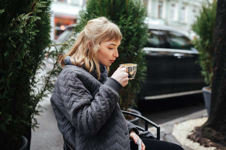 Beautiful lady with blond hair sitting and drinking coffee on city street 스톡 콘텐츠 - 126025216