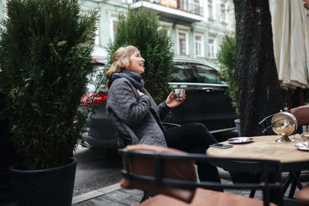 Joyful lady with blond hair sitting with cup of coffee in hand and happily looking aside on street