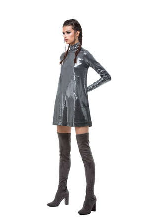 Young lady standing in dress in sequins and knee high boots on white background isolated