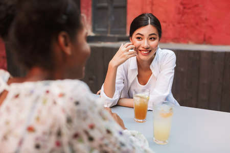 Cheerful girl in white shirt with drink happily looking at friend while spending time in courtyard of cafe