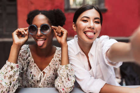 Two pretty girls happily showing tongues while taking photos together spending time in courtyard of cafe