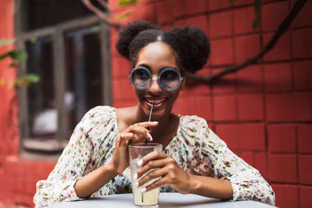 Pretty african girl in blouse and sunglasses joyfully looking aside while drinking cocktail in cozy courtyard of cafe