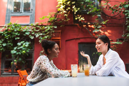 Two beautiful girls happily talking together with cocktails while spending time in cozy courtyard of cafe
