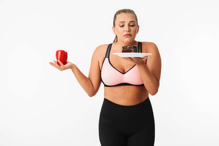 Young woman with excess weight in sporty top thoughtfully choosing between pepper and chocolate cake over white background isolated