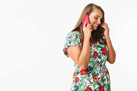 Beautiful smiling girl in colorful dress happily talking on cellphone over white background isolated