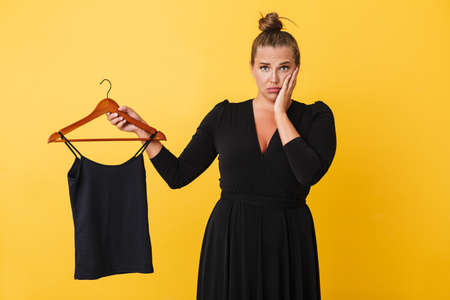 Young woman in black dress amazedly looking in camera while holding hanger with black top over yellow background