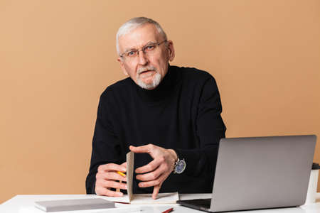 Old man with gray hair and beard in eyeglasses and sweater sitting at the table with laptop and notebook thoughtfully looking in camera over beige background isolated