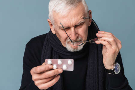 Old pensive sick man with gray hair and beard in eyeglasses and scarf thoughtfully looking on pills over blue background isolated Foto de archivo