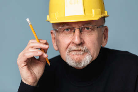 Close up old handsome man with gray beard in eyeglasses and yellow safety helmet thoughtfully looking in camera while holding pencil in hand over blue background