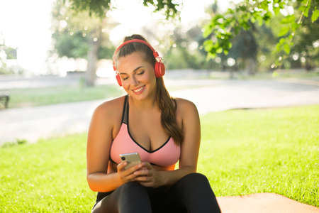 Young beautiful smiling plus size woman in pink sporty top and leggings with red headphones happily using cellphone while spending time in park Stock Photo