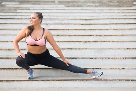 Beautiful smiling plus size girl in sporty top and leggings doing sport on stairs joyfully looking aside while spending time outdoor