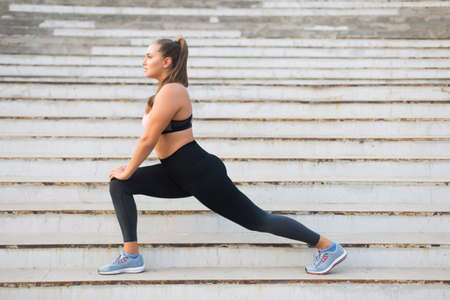 Beautiful plus size girl in sporty top and leggings dreamily stretching on stairs while spending time outdoor