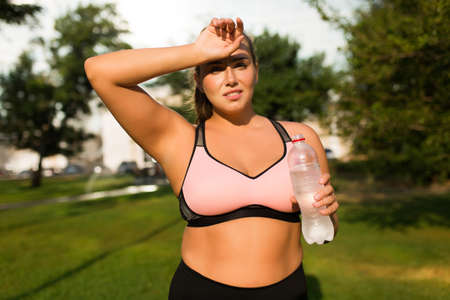 Young tired plus size woman in pink sporty top holding bottle of pure water in hand while thoughtfully looking in camera in city park