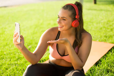 Young joyful plus size woman in pink sporty top and leggings with red headphones happily taking photo on cellphone while sending air kiss in park