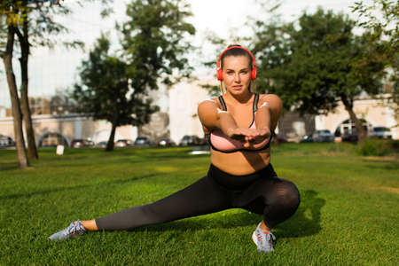 Young attractive plus size woman in sporty top and leggings with red headphones dreamily looking in camera while doing sport on grass in city park Stock Photo