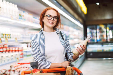 Smiling girl in eyeglasses and striped shirt with shopping cart joyfully looking in camera while holding bottle of milk in hand in modern supermarket