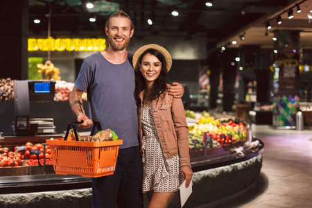 Young beautiful couple happily looking in camera with basket full of products while spending time together in modern supermarket