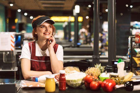 Young cheerful female cashier in uniform joyfully looking aside with products on cash line near while working in modern supermarket
