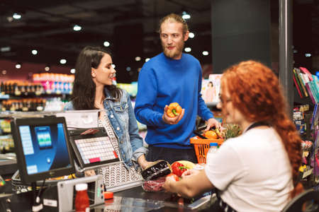 Young smiling couple standing near cashier desk while happily buying products together in modern supermarket