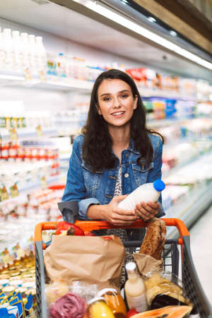 Beautiful smiling girl in denim jacket with trolley full of products dreamily looking in camera while holding bottle of milk in hands in dairy department of modern supermarket Stock fotó