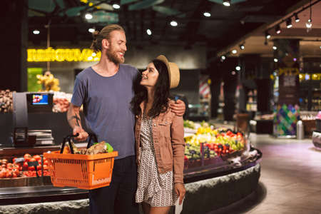 Young beautiful couple happily looking at each other with basket full of products while spending time together in modern supermarket