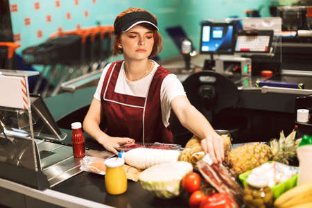 Young female cashier in uniform thoughtfully looking on products wwhile working in modern supermarket