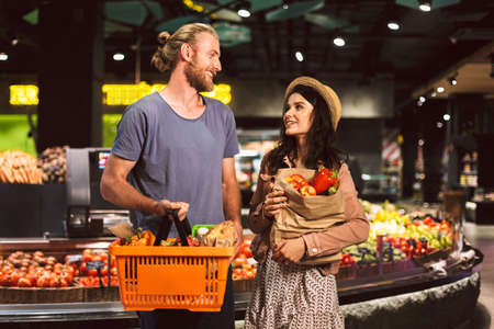 Young smiling guy and pretty girl happily looking at each other with basket and paper grocery bag full of products in supermarket