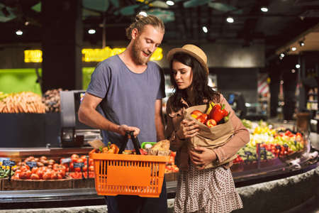 Young guy and girl dreamily looking on basket and paper grocery bag full of products in supermarket