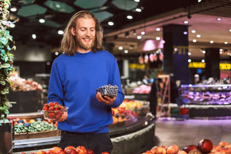 Cheerful man in dark blue sweater happily holding blueberries and strawberries in hands in supermarket Stock Photo