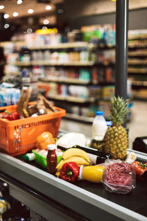 Close up shopping basket and products on cashier desk in supermarket