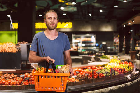 Young smiling man dreamily looking in camera holding basket full of products in hand in supermarket