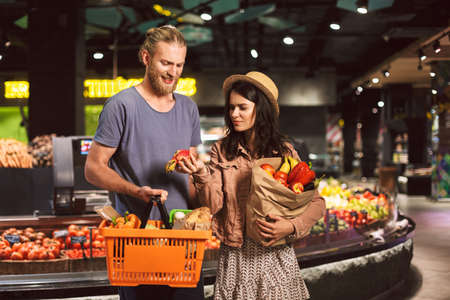 Young guy and girl with basket and paper grocery bag full of products in hands thoughtfully looking on exotic fruit in supermarket Standard-Bild