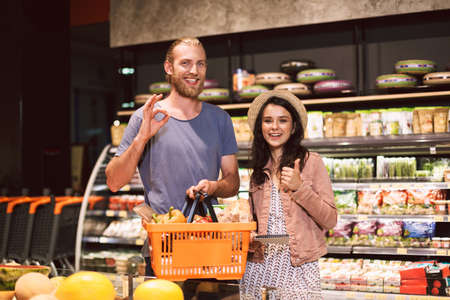 Young smiling guy and cute girl in hat with shopping list in hand happily looking in camera with basket full of products in supermarket