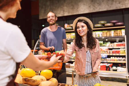 Young beautiful couple with basket full of products happily buying strawberries in supermarket