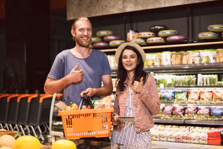 Young smiling guy and pretty girl in hat with shopping list in hand happily looking in camera with basket full of products showing thumb up in modern supermarket