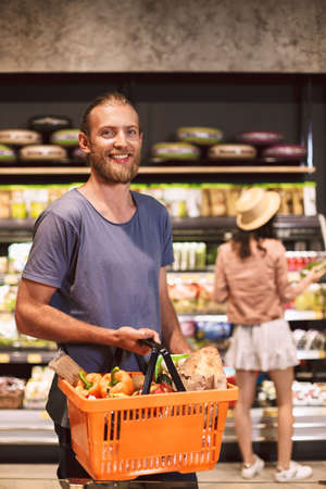 Young smiling man happily looking in camera holding basket full of products in hand with pretty girl in hat on background in supermarket