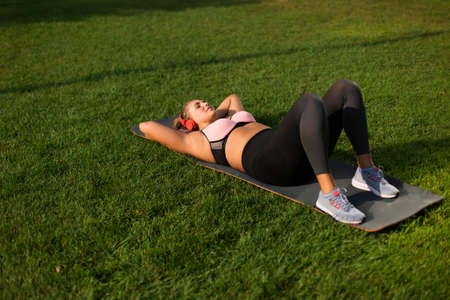 Young pretty plus size woman in pink sporty top and leggings with red headphones dreamily shakes press on yoga mat while spending time in city park