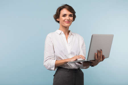 Pretty smiling businesswoman with dark short hair in white shirt holding laptop in hands while happily looking in camera over blue background