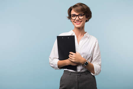 Pretty smiling girl with dark short hair in shirt and eyeglasses holding black folder in hands while happily looking in camera over blue background