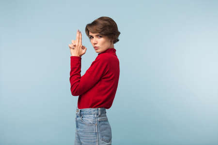 Beautiful serious girl with dark short hair in red sweater and jeans showing gun gesture with hands while thoughtfully looking in camera over blue background Imagens