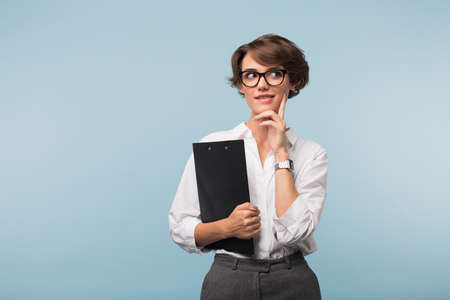 Young pretty woman with dark short hair in shirt and eyeglasses holding folder in hand while dreamily looking aside over blue background Banque d'images