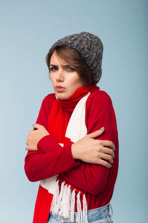 Young upset woman with dark short hair in red sweater,scarf and knitted hat shaking from cold while sadly looking in camera over blue background